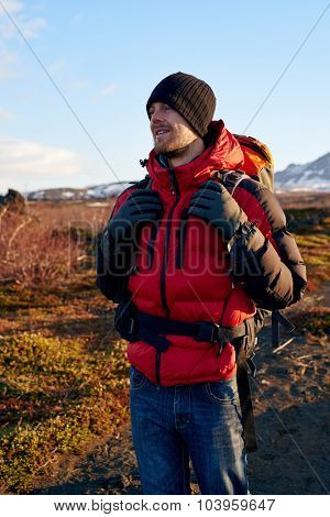 Happy hiking outdoors man at sunrise on mountain trail