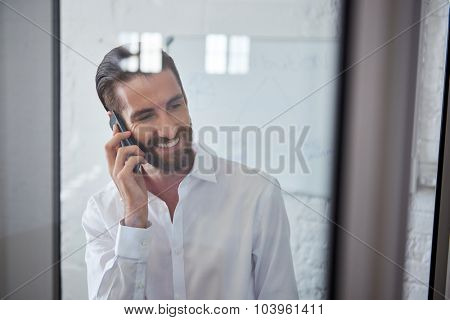young professional happy businessman talking on mobile cell phone in office