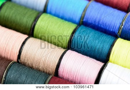 Sewing threads multicolored background macro. Selective focus