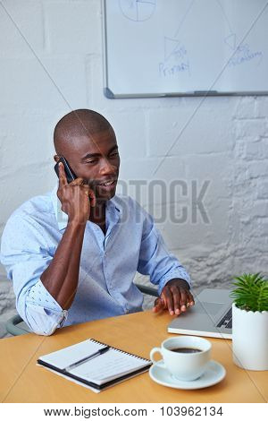 professional african black man talking on mobile cell phone to clients in office