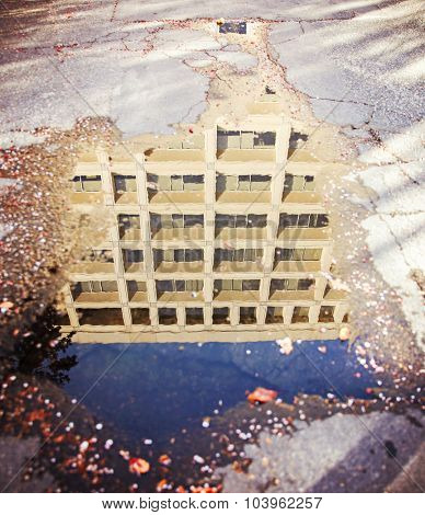 a building reflected in a puddle after a heavy rainstorm toned with a retro vintage instagram filter app or action effect