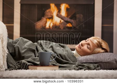 Woman Sleeping Beside Fireplace