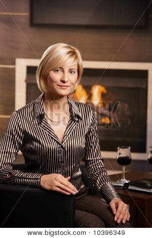 Young Businesswoman Sitting In Front Of Fireplace
