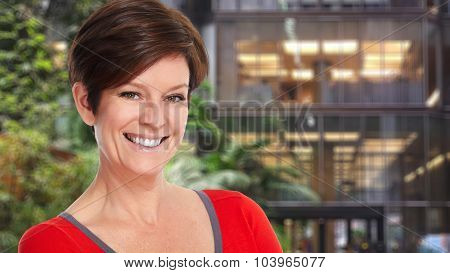Beautiful mature smiling lady over office background.