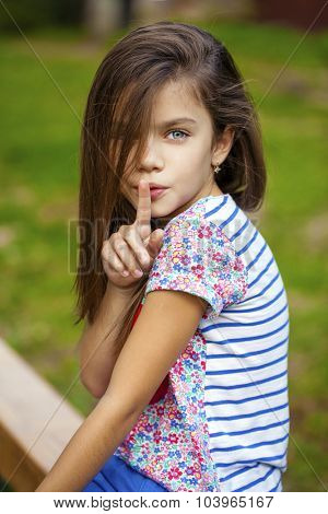 Young beautiful Little girl has put forefinger to lips as sign of silence, outdoors summer