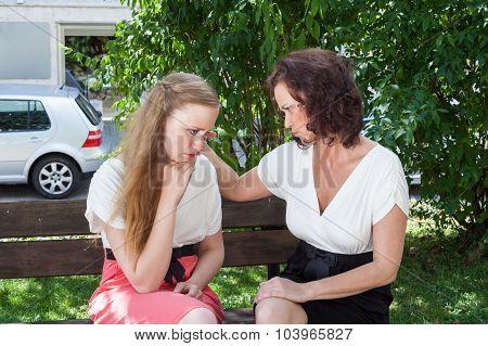 Two Women Having Heartfelt Conversation On Bench