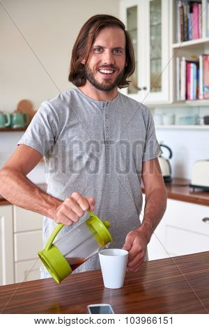 Man preparing coffee for early morning routine in kitchen