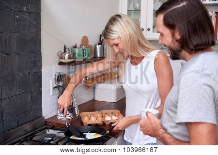 young couple preparing early morning eggs breakfast on stove in home kitchen
