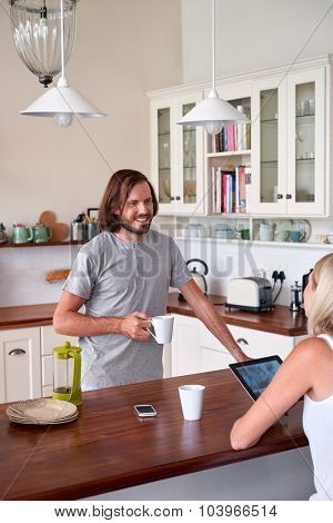 couple relaxing with coffee tablet computer in home kitchen