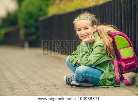Little pretty schoolgirl  sitting on the street with her backpack