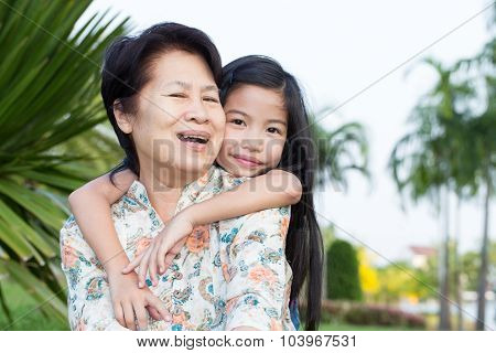 Grandma And Grandchild Hugging In The Park