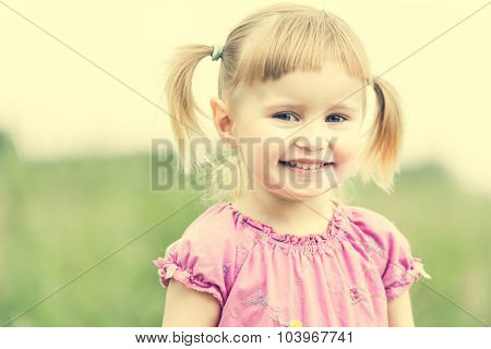 Cute little girl on the meadow in summer day close-up