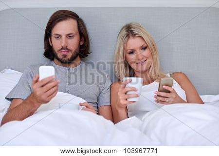 young couple with mobile cellphone relaxing in home bedroom