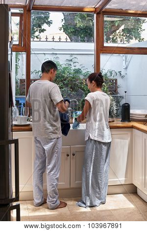 young happy couple doing household chores washing and drying dishes in the kitchen