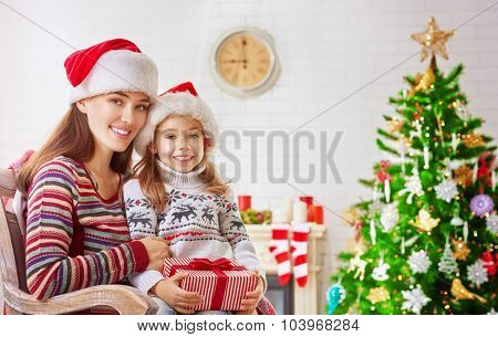 Child with mother sitting near Christmas tree