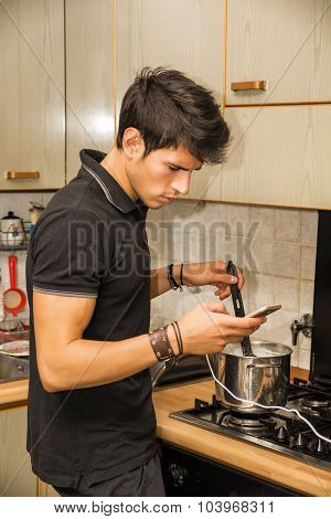 Young Man with Cell Phone Cooking Food on Stove
