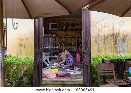 HOI AN, VIETNAM, DECEMBER 14, 2014 : Three women sitting on the floor are chopping some vegetable and spices at home, Hoi An, Vietnam