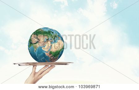 Close up of hand holding tray with Earth planet. Elements of this image are furnished by NASA