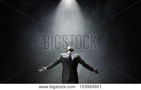 Businessman with hands spread apart on dark background