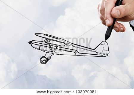 Person hand drawing old airplane on sky background