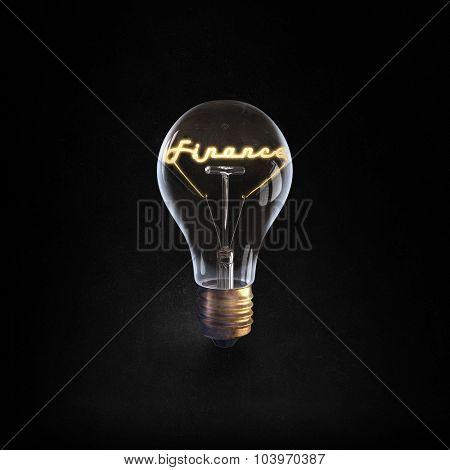 Glowing glass light bulb with word finance inside