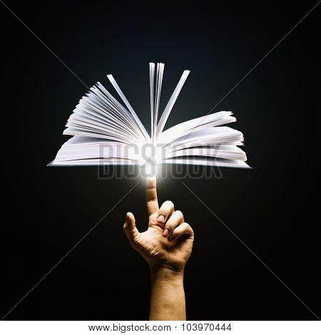Close up of man hand pointing with finger at book