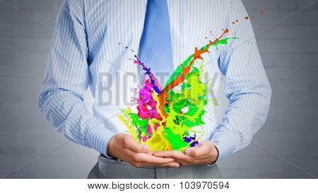 Close up of businessman with paint splashes in hands