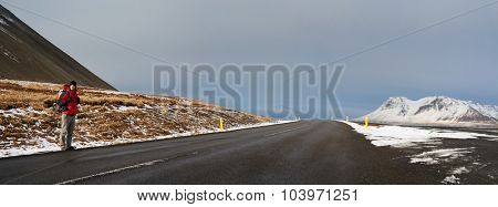 Shoestring budget traveler backpacking hitchhiking through Iceland, waiting for a ride on empty road in snowy winter conditions