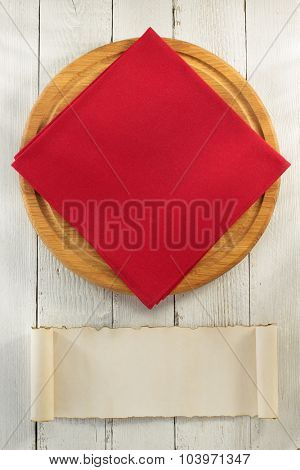 cloth napkin and cutting board on wooden background