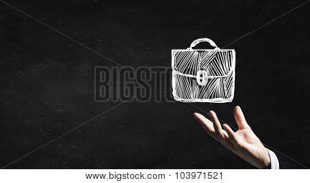 Businessman hand holding chalk drawn briefcase on blackboard background