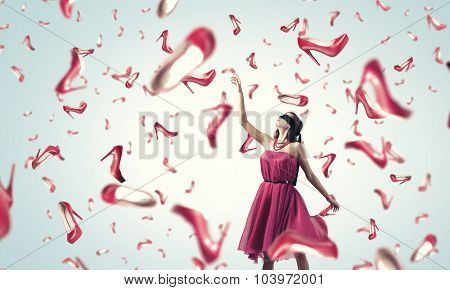 Young woman in dress and many falling shoes