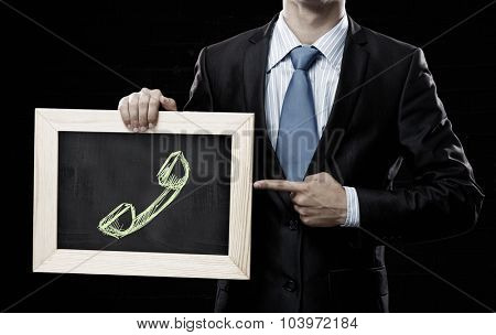Unrecognizable businessman holding chalkboard with calls concept