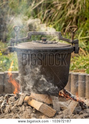 Black cast-iron kettle with fare placed on fire