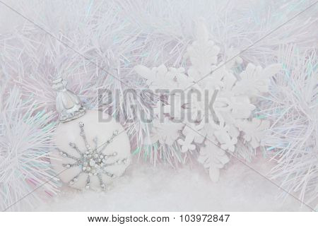 Christmas white bauble and snowflake decorations on snow with decorative tinsel  background.