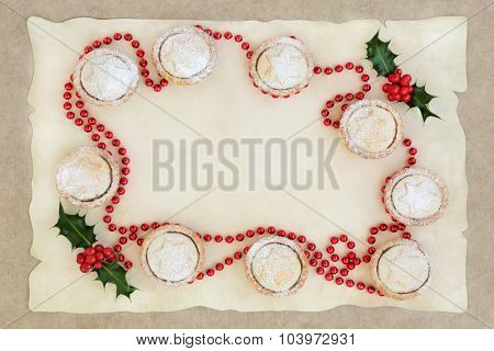 Abstract christmas background border with mince pie cakes, holly and red bead decoration on parchment and old grunge paper.