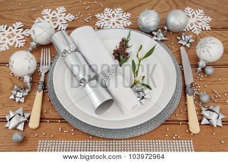 Christmas holiday dinner place setting with plates, napkin, cutlery, silver bauble decorations and mistletoe over oak table background.