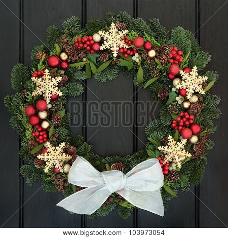 Christmas wreath with gold snowflake and red bauble decorations, holly, mistletoe and winter greenery over dark oak front door background.