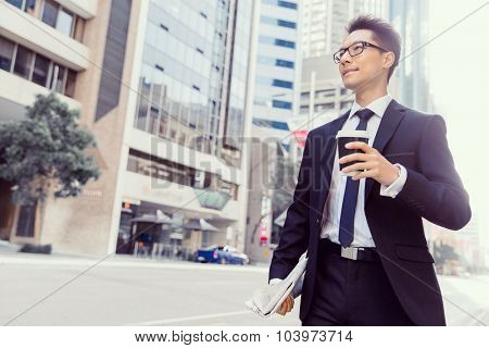 Businessman swalking in street and holding a coffee