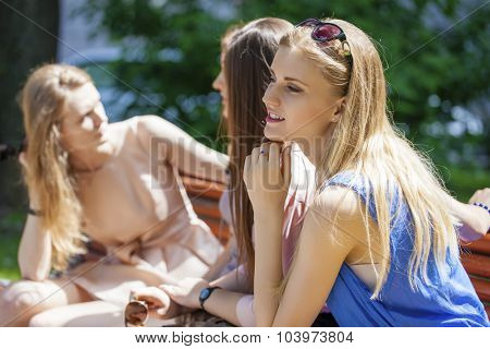 Close up portrait of four urban women outside Sitting On Bench In summer Park
