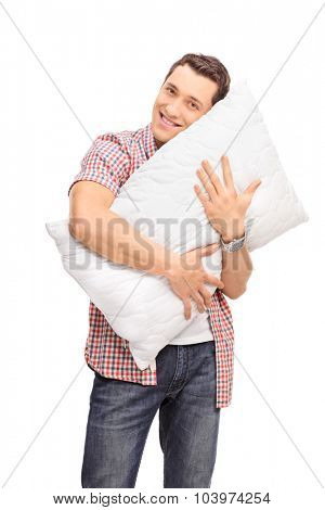 Vertical shot of a young man hugging a white pillow and looking at the camera isolated on white background