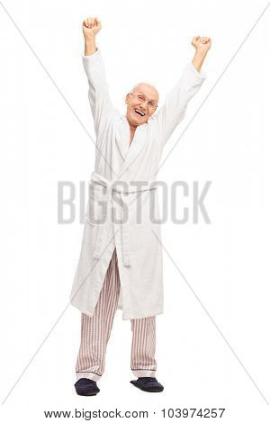 Full length portrait of a senior man in a white bathrobe stretching himself isolated on white background