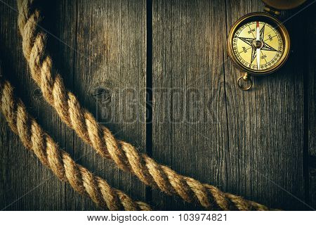 Antique brass compass and rope over wooden background