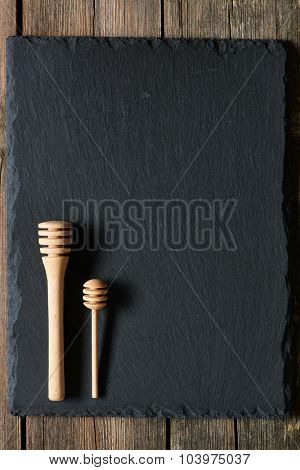 Wooden honey dipper on slate background