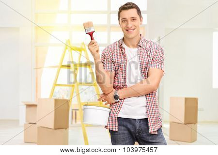 Cheerful man holding a paintbrush and a color bucket in a new apartment with a few cardboard boxes and a yellow ladder behind him