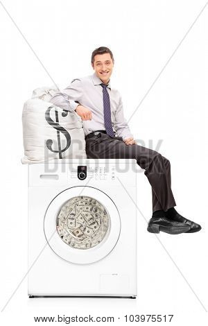 Vertical shot of a young businessman sitting on a washing machine full of money and leaning on a bag with a dollar sign on it isolated on white background
