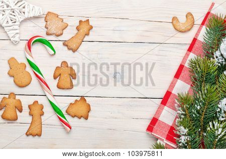 Christmas background with candy cane, gingerbread cookies and snow fir tree. View from above