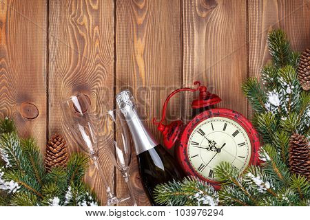 Christmas wooden background with clock, snow fir tree and champagne