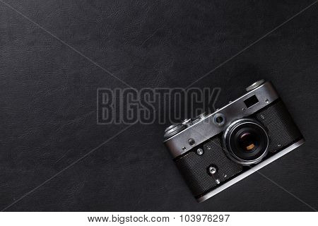 Vintage film camera over leather desk table. Top view with copy space
