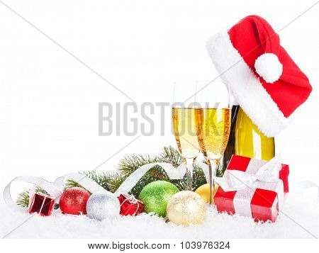 Champagne, christmas decor and santa hat over snow and fir tree with copy space