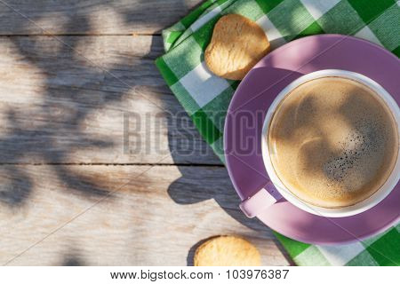 Coffee cup and cookies on garden table. Top view with copy space